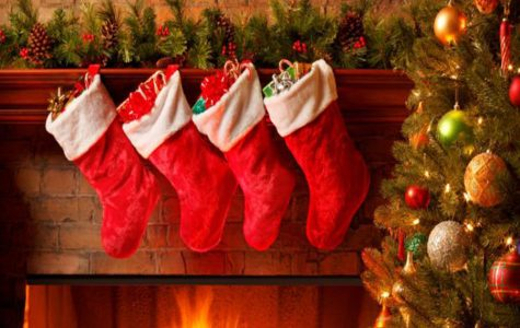 Photo courtesy of History.com via Google Images. A photo of four stockings over a lit Christmas fireplace.